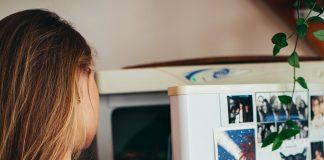 A woman standing at a fridge